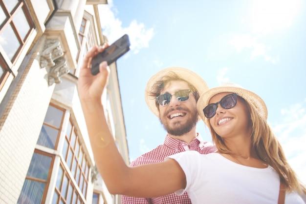 Sourire couple de prendre un selfie