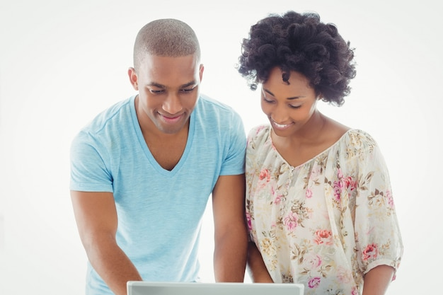Sourire couple utilisant un ordinateur portable ensemble à la maison