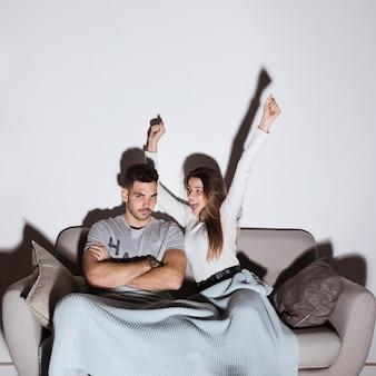 Sourire dame et mec en colère devant la télé sur un canapé