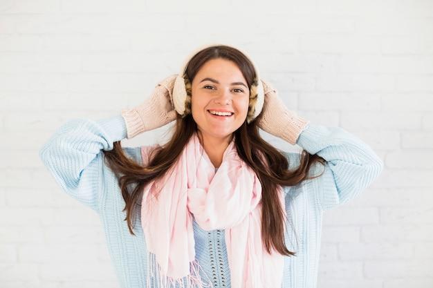 Sourire dame en mitaines, cache-oreilles et foulard
