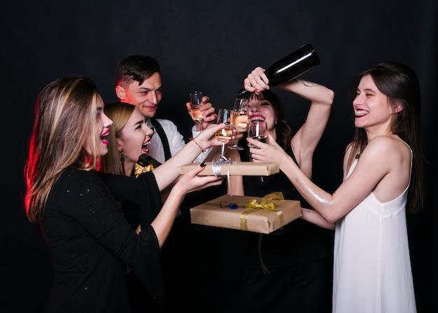 Sourire dames et gars en tenue de soirée avec bouteille, verres de boissons et boîtes à cadeaux