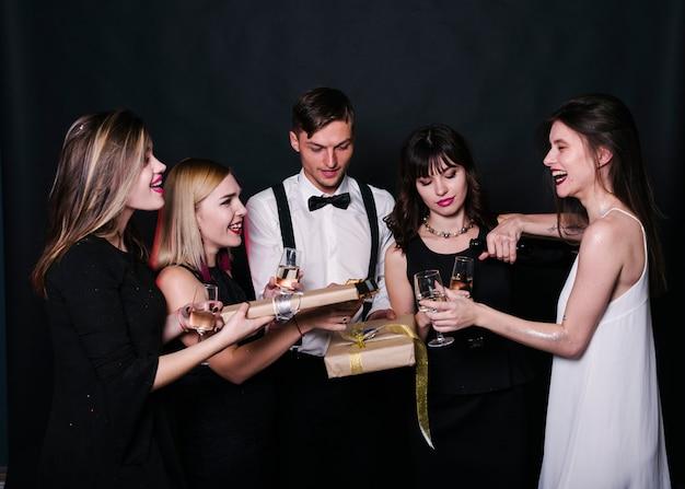 Sourire dames et gars en tenue de soirée avec des verres de boissons et des boîtes à cadeaux