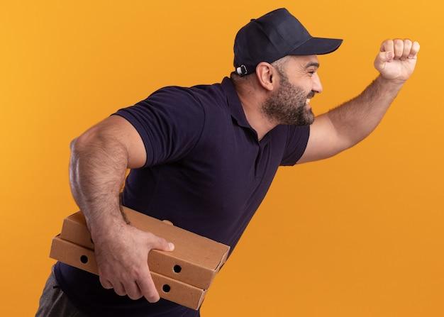 Sourire debout en vue de profil livreur d'âge moyen en uniforme et cap tenant des boîtes à pizza et montrant le geste en cours d'exécution isolé sur mur jaune