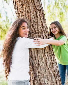 Sourire deux filles étreignant grand tronc d'arbre
