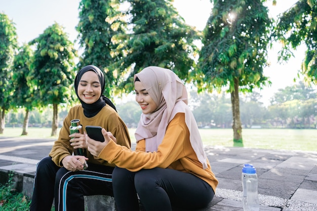 Sourire de deux filles musulmanes asiatiques à l'aide d'un téléphone portable ensemble lors de la tenue d'une bouteille après le sport ensemble dans l'après-midi dans le parc