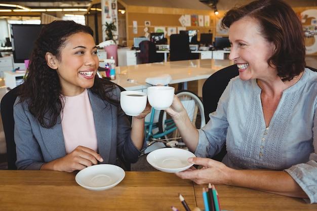 Sourire des dirigeants d'entreprise grillage des tasses à café