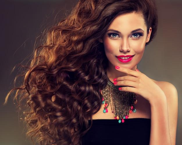 Sourire doux sur le visage de la jeune femme aux cheveux bruns aux longs cheveux volumineux