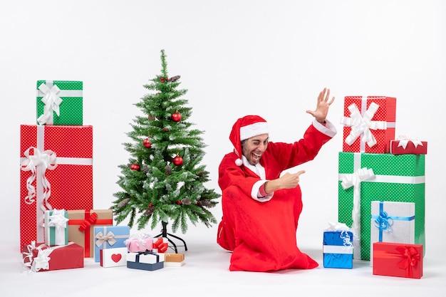 Sourire drôle de jeune homme habillé en père noël avec des cadeaux et arbre de noël décoré assis sur le sol en pointant quelque chose sur le côté gauche sur fond blanc