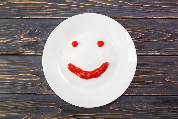 Sourire avec du ketchup dans une assiette sur une surface en bois