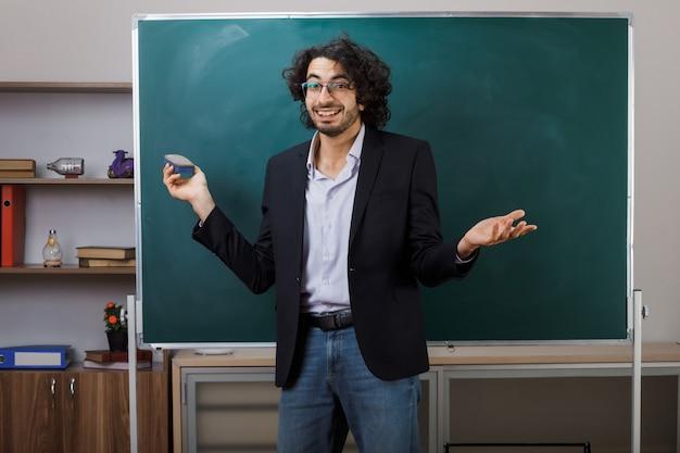 Sourire écartant les mains jeune enseignant portant des lunettes debout devant le tableau noir tenant une éponge dans la salle de classe