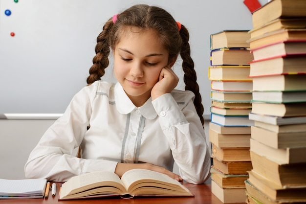 Sourire écolière lisant un livre, assis près du tableau blanc dans la salle de classe