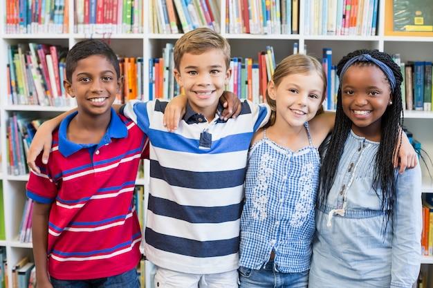 Sourire, écoliers, debout, bras, autour de, bibliothèque