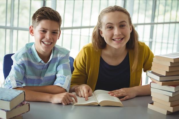 Sourire, écoliers, lecture livres, dans, bibliothèque, à, école