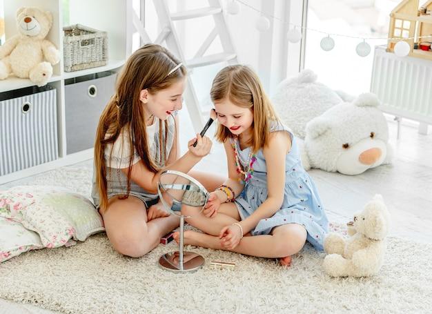 Sourire enfants filles appliquant des cosmétiques de maquillage dans la chambre des enfants