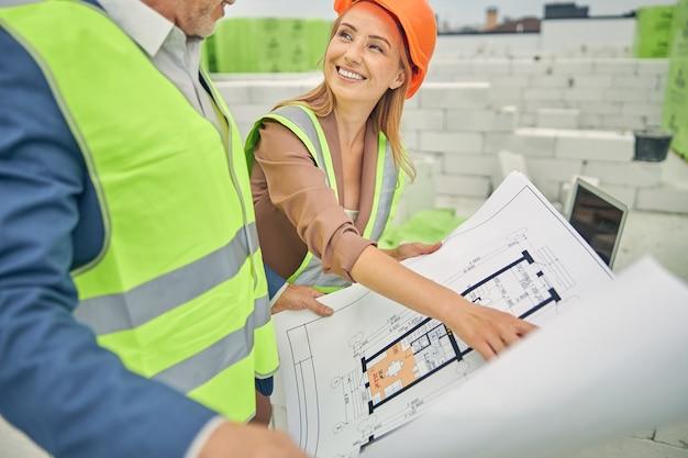 Sourire entrepreneur féminin gai dans un casque en regardant un ingénieur civil senior masculin