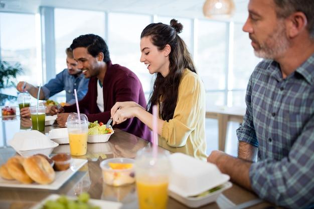 Sourire équipe commerciale créative ayant un repas au bureau