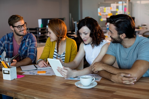 Sourire équipe commerciale créative discutant sur tablette numérique au bureau au bureau