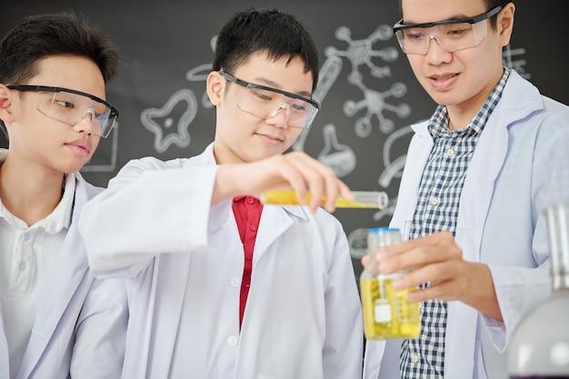 Sourire étudiant à lunettes verser le réactif dans le bécher dans les mains de l'enseignant à la classe de chimie