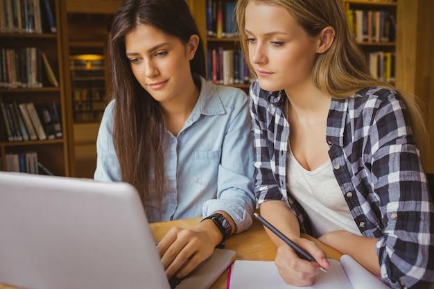 Sourire d'étudiants à l'aide d'un ordinateur portable dans la bibliothèque