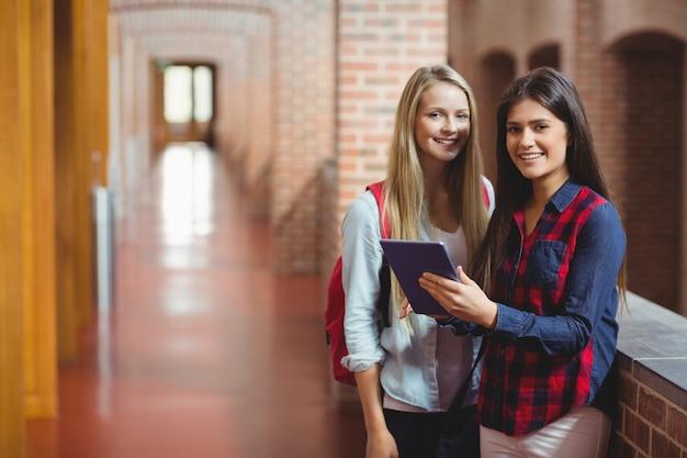 Sourire d'étudiants à l'aide d'une tablette ensemble à l'université