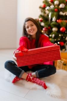 Sourire excité jolie femme en pull rouge assis à la maison à l'arbre de noël déballage des cadeaux et coffrets cadeaux