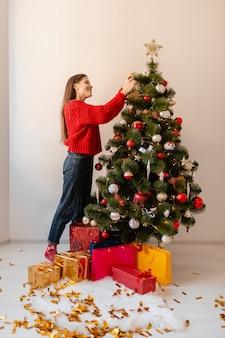 Sourire excité jolie femme en pull rouge debout à la maison décoration arbre de noël entouré de cadeaux et coffrets cadeaux