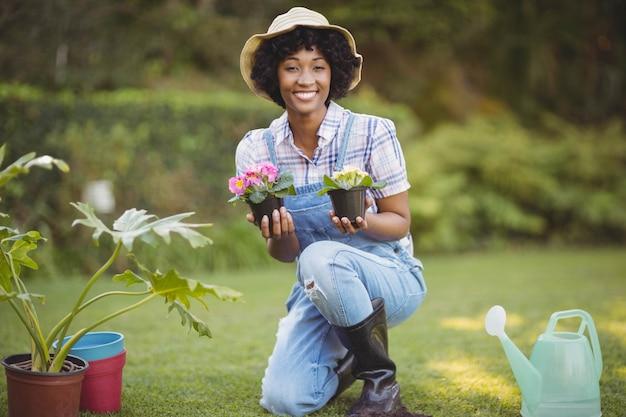 Sourire femme accroupie dans le jardin tenant des fleurs