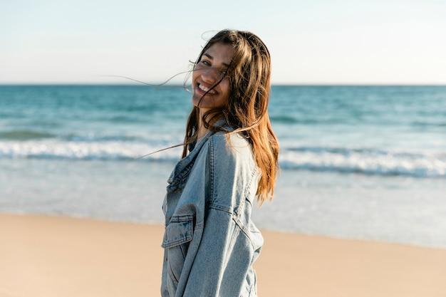 Sourire femme adulte sur la plage en regardant la caméra