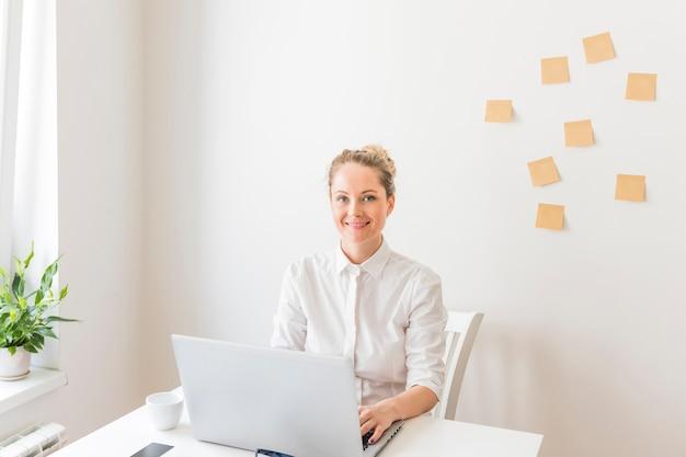Sourire de femme d'affaires à l'aide d'un ordinateur portable avec des notes autocollantes sur le mur