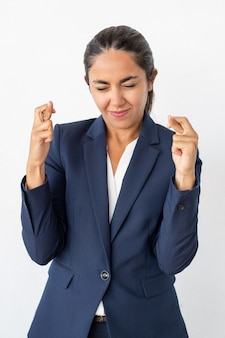 Sourire femme d'affaires avec les doigts croisés