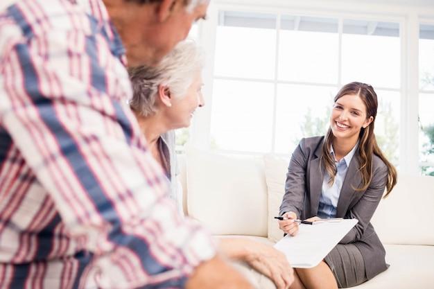 Sourire, femme affaires, montrer documents, à, couple aîné, dans, salle de séjour
