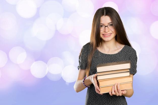 Sourire de femme d'affaires tenant une pile de livres