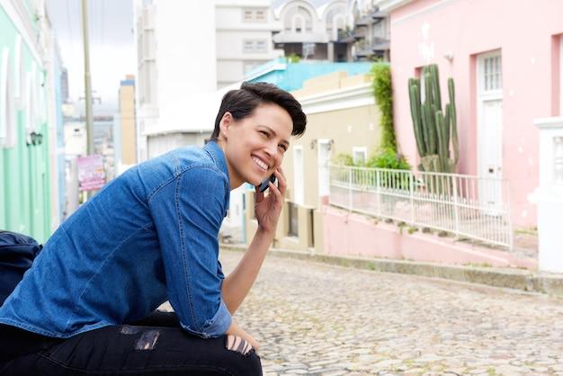 Sourire de femme d'affaires en utilisant un téléphone cellulaire