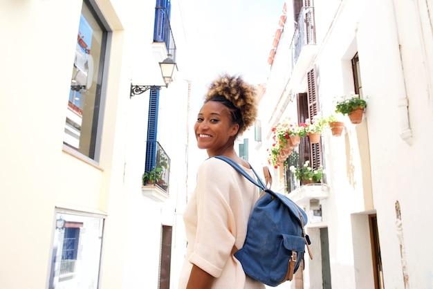 Sourire de femme africaine marchant dans la rue étroite avec un sac