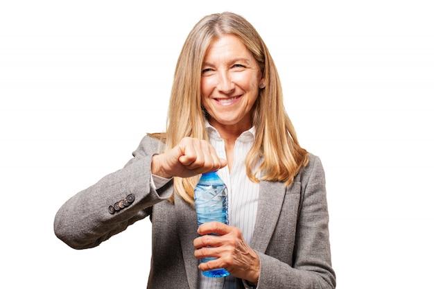 Sourire femme âgée d'ouvrir une bouteille d'eau