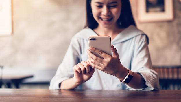 Sourire de femme asiatique à l'aide de sms de smartphone sur le café.