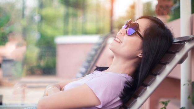 Sourire de femme asiatique allongée sur la chaise en bois et portant des lunettes de soleil.