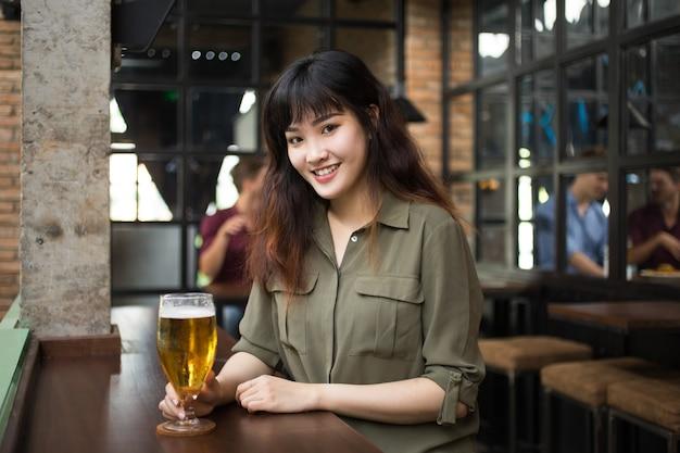 Sourire, femme asiatique, boire de la bière au pub