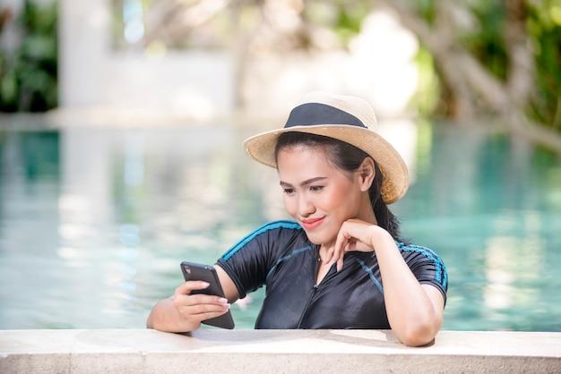 Sourire de femme asiatique avec chapeau de paille à l'aide de téléphone portable