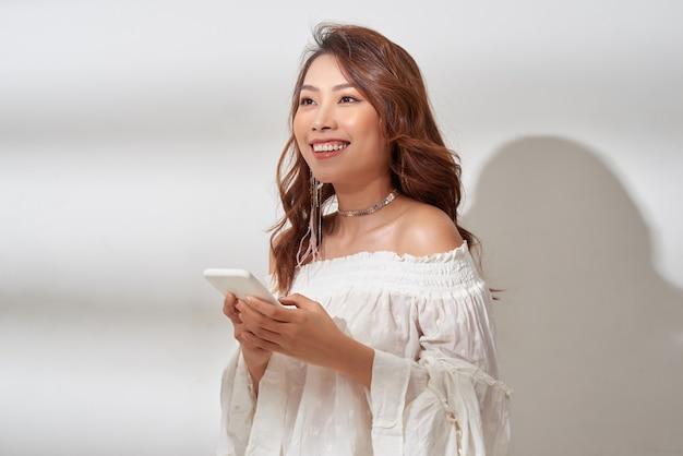 Sourire, femme asiatique positive avec beau visage émotionnel, écouter de la musique sur blanc