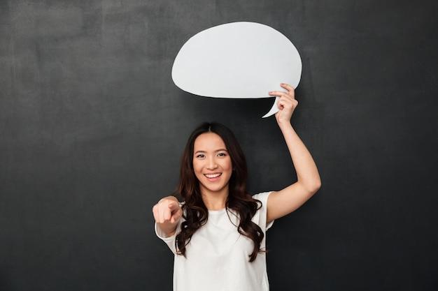 Sourire, femme asiatique, tenue, vide, bulle discours, au-dessus, elle, tête, et, pointage doigt, sur, appareil photo, isolé, sur, gris foncé, mur