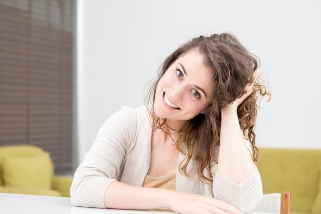 Sourire, femme, cheveux ondulés, assise, table, maison