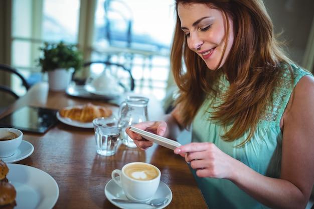 Sourire, femme cliquant photo de café depuis un téléphone mobile
