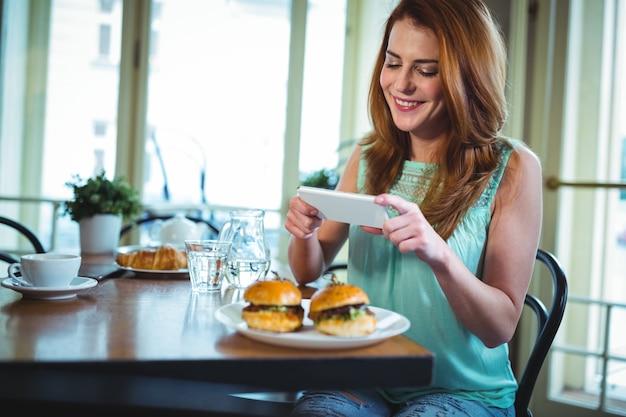 Sourire, femme cliquant photo de hamburger de téléphone mobile