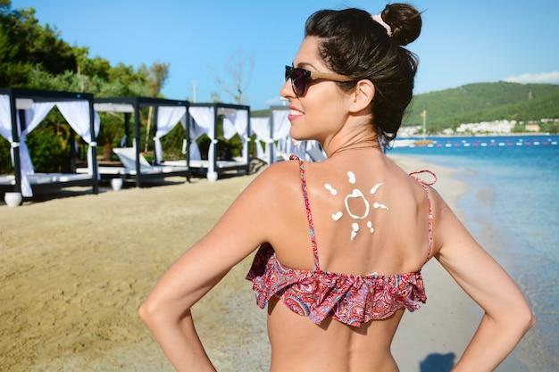 Sourire femme avec de la crème solaire sur son dos