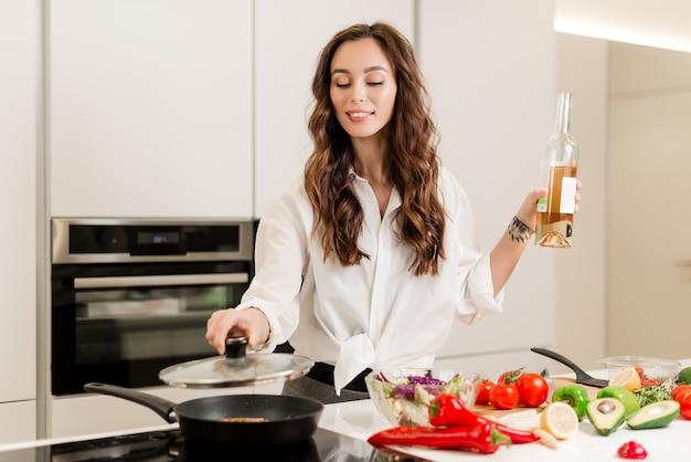 Sourire, femme, cuisine, steak de poisson frais, vin blanc, légumes, cuisine