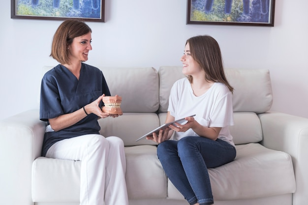 Sourire femme dentiste montrant le modèle de dents au patient tenant une tablette numérique