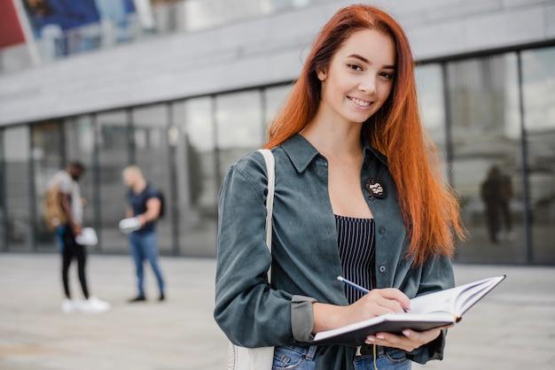 Sourire femme élégante avec cahier