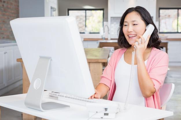 Sourire femme enceinte dans un appel sur ligne terrestre à la maison