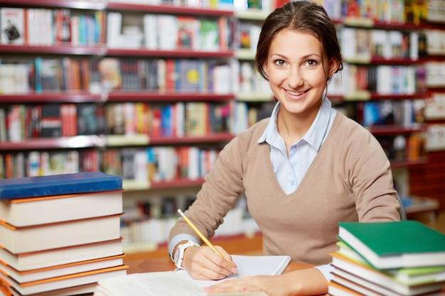 Sourire, femme, étudier dans la bibliothèque